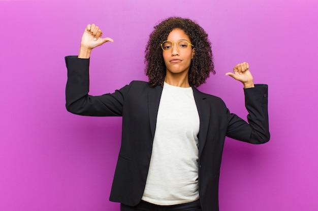 Mulher de negócios preto jovem se sentindo orgulhoso, arrogante e confiante, olhando satisfeito e bem sucedido, apontando para si mesmo