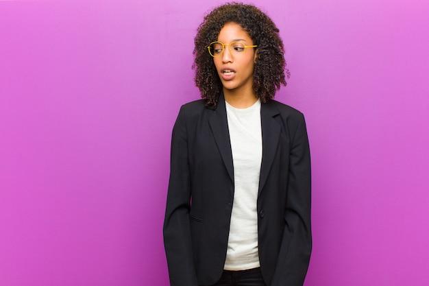 Mulher de negócios preto jovem sentindo chocado, feliz, espantado e surpreso, olhando para o lado com a boca aberta