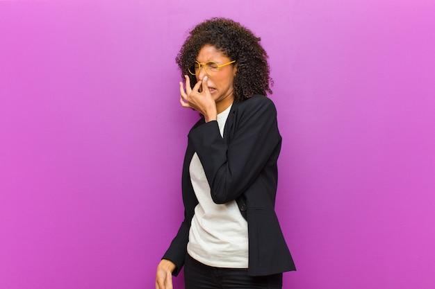Mulher de negócios preto jovem sentindo nojo, segurando o nariz para evitar cheirar um fedor sujo e desagradável