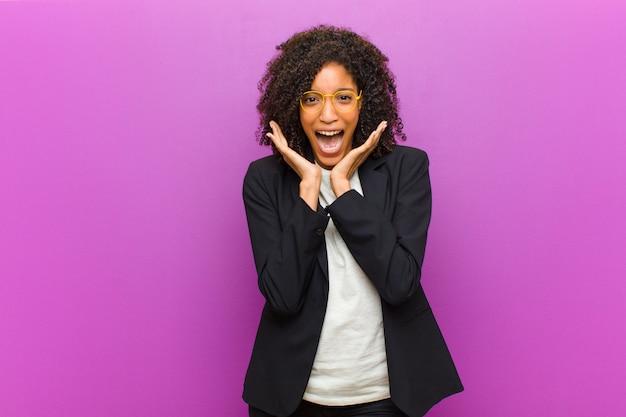 Mulher de negócios preto jovem sentindo-se chocado e animado, rindo, espantado e feliz por causa de uma surpresa inesperada