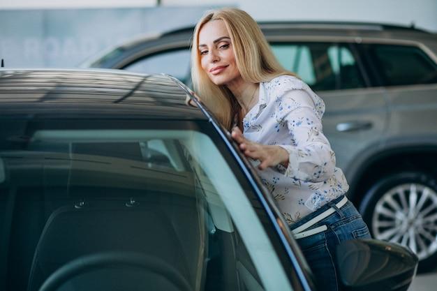 Mulher de negócios, procurando um automóvel móvel em uma sala de exposições de carros