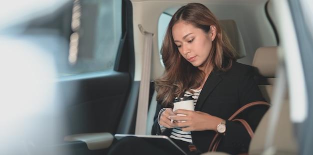 Mulher de negócios profissional trabalhando no carro enquanto se dirigia para o escritório