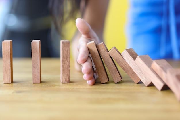 Mulher de negócios protege o bloco de madeira contra quedas, planejamento e seguro de investimento estratégico