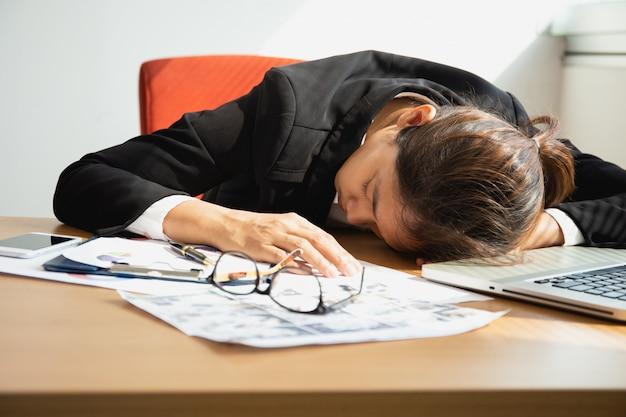Mulher de negócios que dorme na mesa do trabalho com o portátil após o tempo do almoço.