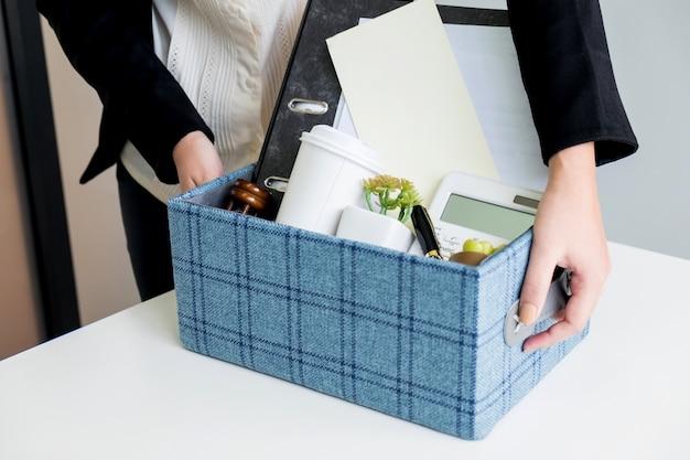 Mulher de negócios que embala pertences pessoais da empresa quando decide resignação e troca de trabalho no futuro