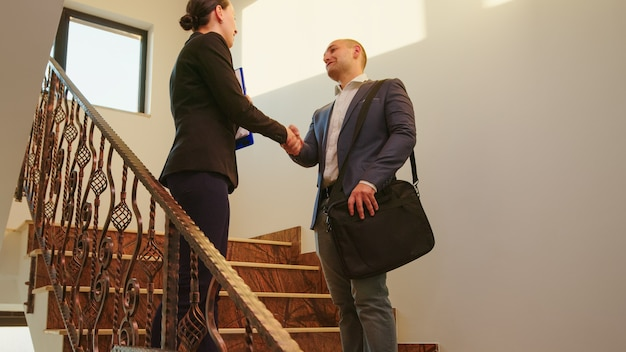 Mulher de negócios que encontra o colega do homem no escritório corporativo cumprimentando com um aperto de mão, dando as boas-vindas e falando nas escadas. equipe de empresários profissionais trabalhando na saudação de edifício financeiro moderno.