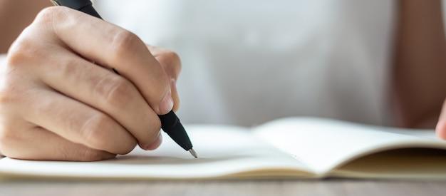 Mulher de negócios que escreve no caderno no escritório, mão da pena de terra arrendada da mulher com assinatura no relatório de papel. conceitos de negócios