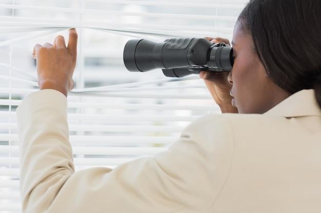 Mulher de negócios que espreita com binóculos através de persianas