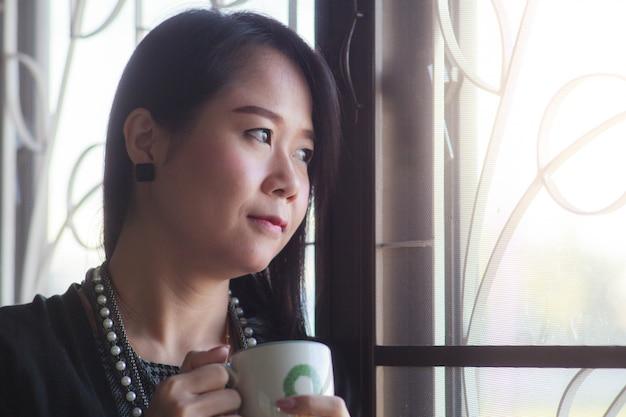 Mulher de negócios que está e que pensa na janela e no café bebendo.