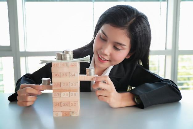 Mulher de negócios que joga o jogo de madeira do bloco com dinheiro e moeda, ideia da estratégia de gestão.