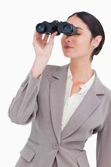 Mulher de negócios que olha através de espiões