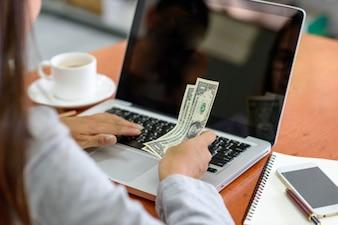 Mulher de negócios que olha taxas de câmbio extrangeiras de um computador portátil.