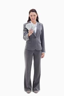 Mulher de negócios que segura muitos dólares de notas de banco