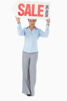 Mulher de negócios que segura o sinal acima de sua cabeça