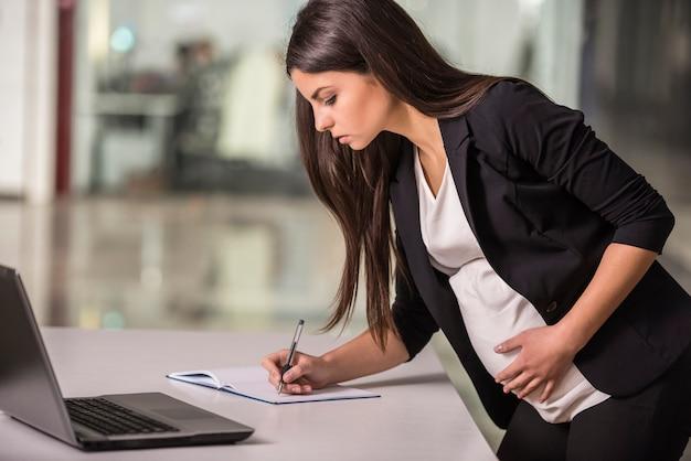 Mulher de negócios que trabalha em seu lugar de funcionamento no escritório.