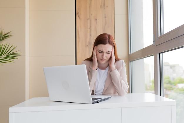 Mulher de negócios que trabalha no computador, sentada no escritório, tem forte estresse e dor de cabeça