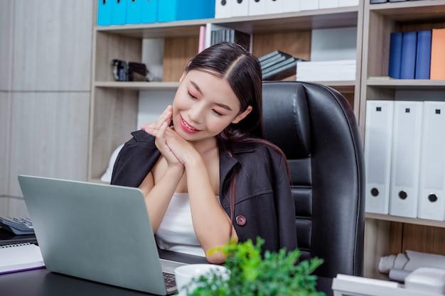 Mulher de negócios que trabalha no escritório com um sorriso ao sentar-se.