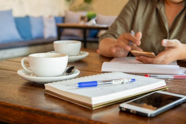 Mulher de negócios que usa o telefone celular no café na ruptura de café.