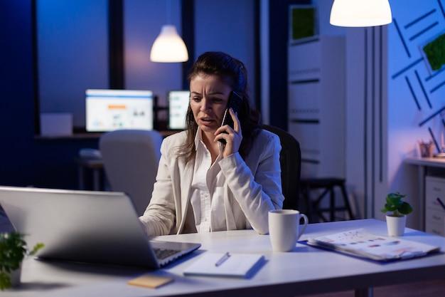 Mulher de negócios recebendo uma ligação no escritório de inicialização à noite, trabalhando no projeto de marketing