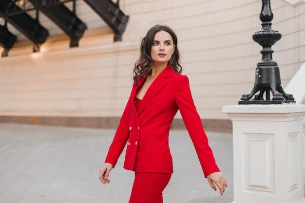 Mulher de negócios rica e sexy linda em um terno vermelho andando na rua da cidade, tendência da moda primavera verão