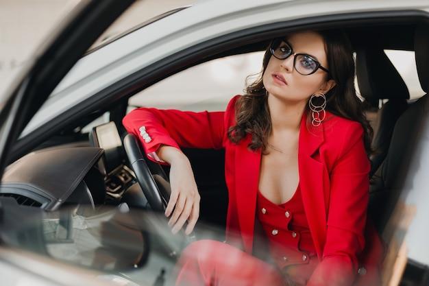 Mulher de negócios rica e sexy linda em um terno vermelho sentada em um carro branco, usando óculos