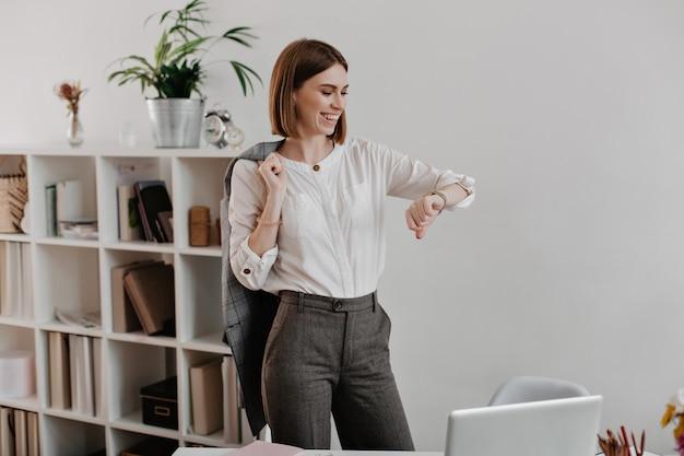 Mulher de negócios rindo em blusa branca e calça cinza está olhando para o relógio de pulso, em pé contra a mobília de escritório.