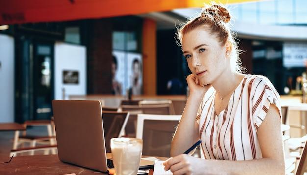 Mulher de negócios, ruiva, caucasiana, com sardas, escrevendo e pensando em algo em um refeitório, enquanto bebe um coquetel e usa um laptop
