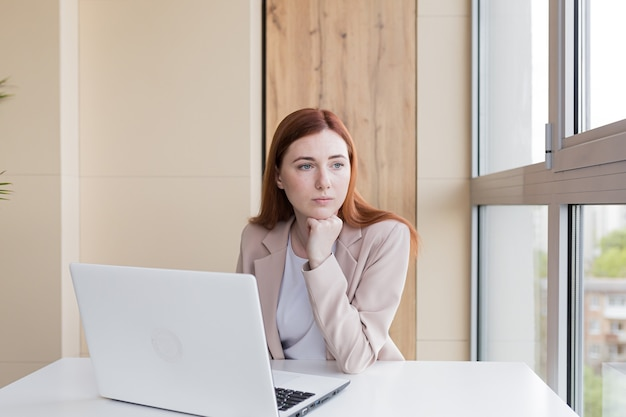 Mulher de negócios ruiva chateada trabalhando no computador, sentada no escritório