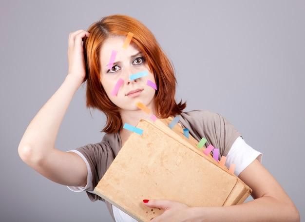 Mulher de negócios ruiva com livro e notas no rosto.