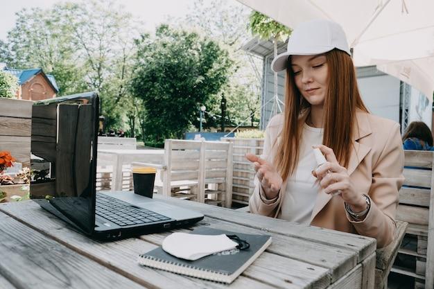 Mulher de negócios ruiva usando gel anti-séptico para desinfetar as mãos em uma mesa de trabalho ao ar livre