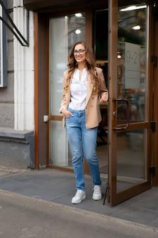 Mulher de negócios, saindo da porta da loja, do lado de fora, caucasiano, mulher, empresário, parado, perto da porta da loja, vestido, jeans, jaqueta, óculos, segurando, maçaneta