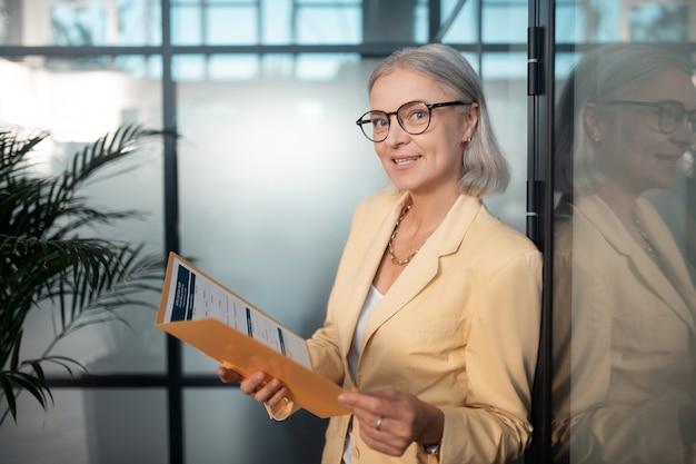 Mulher de negócios satisfeita. closeup retrato de uma mulher de negócios satisfeita usando óculos, segurando uma pasta de papel enquanto olha para a frente dela