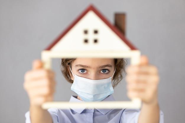 Mulher de negócios segurando a casa modelo usando máscara protetora nas mãos