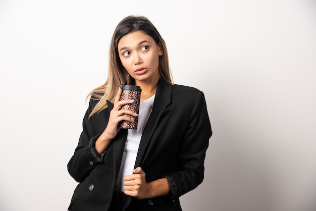 Mulher de negócios, segurando a taça e posando na parede branca.