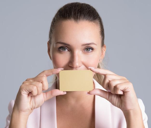 Mulher de negócios segurando o cartão de crédito contra os lábios isolado retrato de estúdio