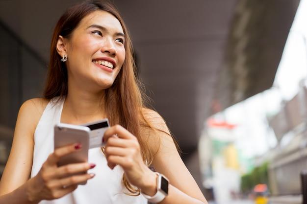 Mulher de negócios, segurando o smartphone com cartão de crédito para pagar compras on-line e-commerce
