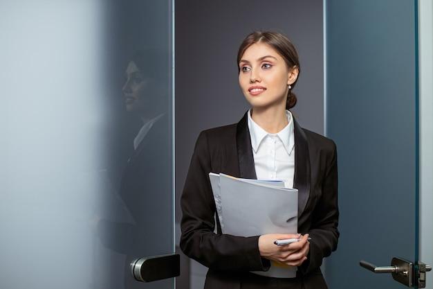 Mulher de negócios, segurando relatórios e olhando para a câmera.