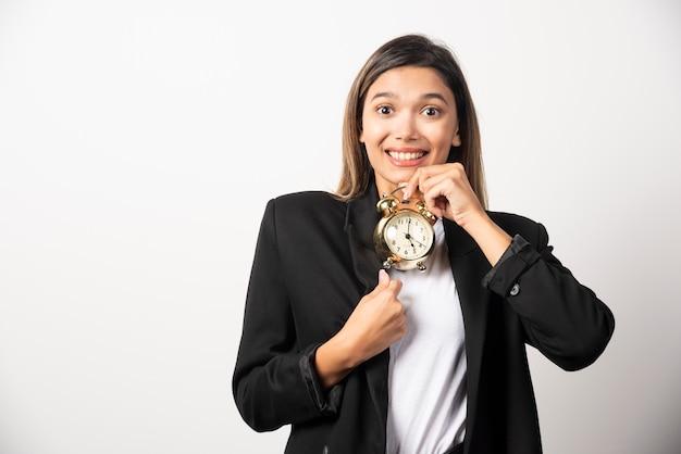 Mulher de negócios segurando um despertador na parede branca.