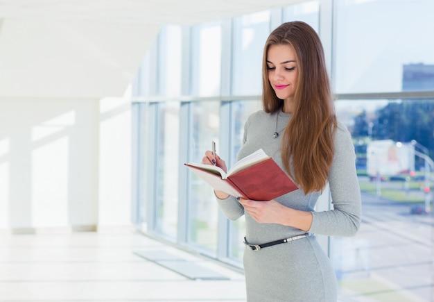 Mulher de negócios, segurando um diário nas mãos, olhando para ele e fazendo anotações com uma caneta