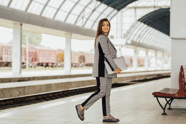 Mulher de negócios segurando um laptop e esperando o trem chegar