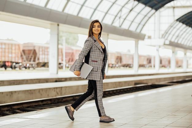 Mulher de negócios segurando um laptop e esperando o trem chegar.