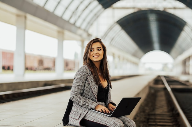 Mulher de negócios segurando um laptop na plataforma de uma estação de trem.