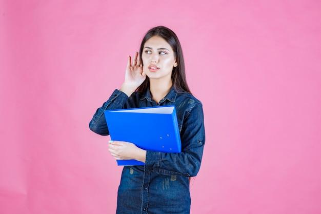 Mulher de negócios segurando uma lista de verificação azul e parece confusa