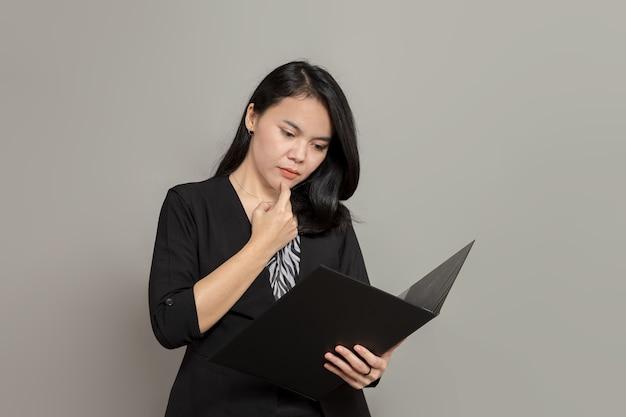 Mulher de negócios segurando uma pasta com uma expressão plana