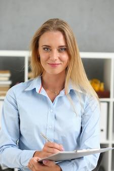 Mulher de negócios segurando uma pasta de prancheta do tablet no escritório
