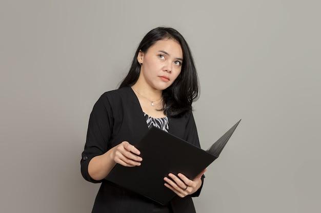 Mulher de negócios segurando uma pasta enquanto imagina a expressão