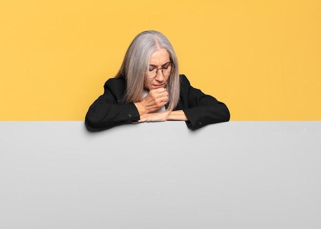Mulher de negócios sênior bonita com cabelo grisalho e quadro cinza
