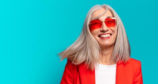 Mulher de negócios sênior bonita com óculos de sol vermelhos