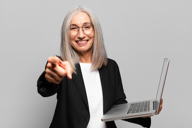 Mulher de negócios sênior bonita com um laptop