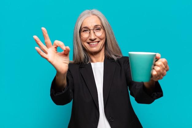 Mulher de negócios sênior bonita com uma xícara de café
